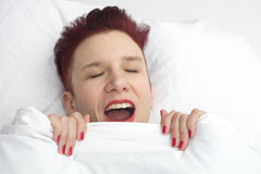 Red-haired woman yawning in bed Royalty Free Stock Photo