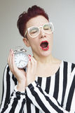 Red-haired woman yawning and holding alarm clock Stock Photography