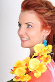 Red-haired woman with yellow orchid Stock Image