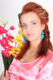 Red-haired woman with yellow and pink orchid Royalty Free Stock Photography