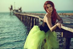 Red haired womanstanding in the sea water leaning on the pier. Mermaid coming out of water and trying to make first steps Royalty Free Stock Images