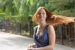 Red haired women dancing outdoors in city park. Royalty Free Stock Image