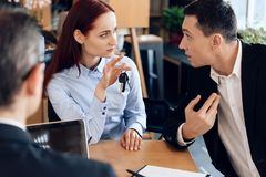 Red-haired woman is holding on finger keys sitting next to adult man in lawyer`s office. stock photo