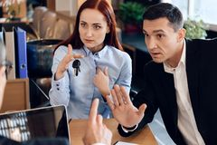 Red-haired woman is holding on finger keys sitting next to adult man in lawyer`s office. stock image