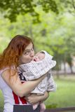 Red-haired woman kissing her little baby in summer park. Child cries in her mother& x27;s arms. Red-haired women kissing her little baby in summer green park royalty free stock images