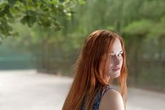 Red haired women looking back Stock Photo
