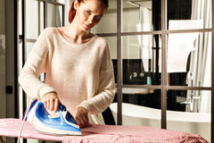 Red-haired young beautiful woman ironing clothes Royalty Free Stock Image
