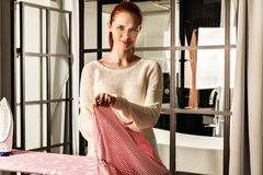 Red-haired young beautiful woman ironing clothes Royalty Free Stock Images