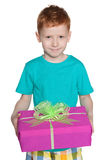Red-haired young boy holds a gift box Royalty Free Stock Images