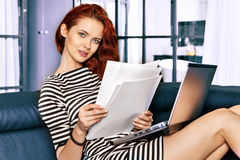 Red-haired young business woman or student girl working with computer at indoor Stock Images