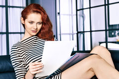 Red-haired young business woman or student girl working with documents at indoor Royalty Free Stock Photo