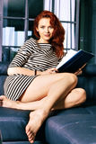 Red-haired young business woman or student girl working with documents at indoor Royalty Free Stock Image