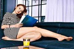 Red-haired young business woman or student girl working with documents at indoor Stock Image