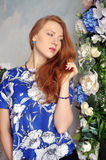 Red-haired young girl in blue blouse tilting her head holding her hair Royalty Free Stock Images