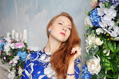 Red-haired young girl in blue blouse tilting her head holding her hair Stock Photos