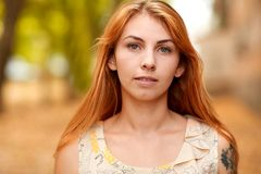 Red-haired young girl with gray eyes in the park. stock photography