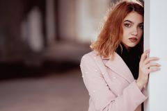 Red-haired young girl in a pink coat posing in an empty room, leaning against the wall royalty free stock photo
