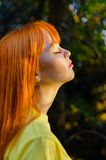 Taking a deep breath relaxing young girl against s. Red haired young girl taking a deep breath against sun royalty free stock photo