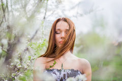 Red-haired young lady with closed eyes in spring orchard Royalty Free Stock Photo
