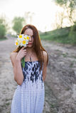 Red-haired young lady in floral dress with bouquet of daffodils Royalty Free Stock Photography