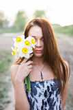 Red-haired young lady in floral dress with bouquet of daffodils Royalty Free Stock Photos