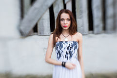 Red-haired young lady in floral dress near abandoned building Royalty Free Stock Image