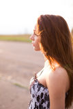 Red-haired young lady in floral dress at sunset Royalty Free Stock Images