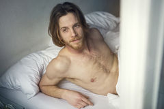 Red-haired young man lying in bed Royalty Free Stock Images