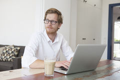 Red-haired young man sitting at table with his laptop Stock Photos