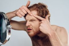 Red haired young man squeeze out pimple. On forehead, looking into mirror. Morning hygiene procedures. Isolated on grey background. Studio portrait. Acne. Skin stock photo