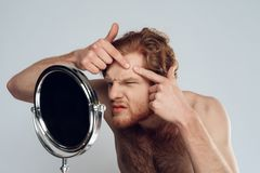 Red haired young man squeeze out pimple. On forehead, looking into mirror. Morning hygiene procedures. Isolated on grey background. Studio portrait. Acne. Skin royalty free stock image
