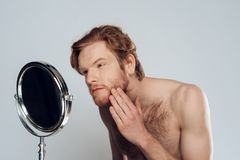 Red haired young man strokes beard, looking into mirror. stock photo