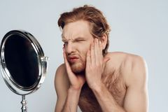 Red haired young man stroking beard royalty free stock image