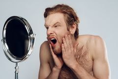 Red haired young man stroking beard stock image