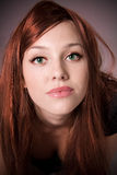 Red haired young woman. Portrait of pretty red haired young woman, studio background Stock Photo