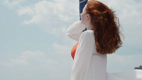 Red haired young woman directs her face to the sun wind shakes her hair stock video footage