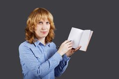 Red haired young woman holding an open notebook Royalty Free Stock Photography