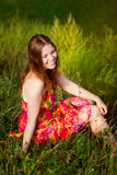 Red-haired young woman with long ginger hair and closed eyes. Sitting on grass and smiling on hot sunny day. Carefree, freedom and leisure concept stock photography
