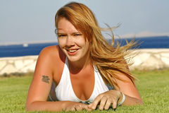Red-haired young woman lying on the grass in a white swimsuit Stock Images