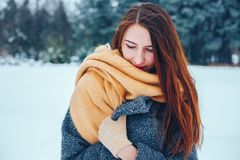 Red-haired young woman with a red scarf in a winter forest Stock Images