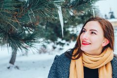 Red-haired young woman with a red scarf in a winter forest Stock Photos