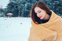 Red-haired young woman with a red scarf in a winter forest Royalty Free Stock Photography