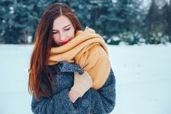 Red-haired young woman with a red scarf in a winter forest Royalty Free Stock Images
