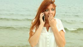 Woman speaking on the phone on beach, full HD. Red haired young woman speaking on the phone on beach. Emotional face expression. Full HD 1920X1080P stock footage