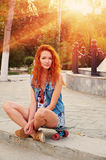 Red haired young women sitting on skateboard with her legs crossed backlit by sun Royalty Free Stock Image