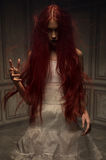 Red haired zombie woman. In white cotton dress Stock Photo