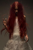 Red haired zombie woman. In white cotton dress royalty free stock photography