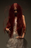 Red haired zombie woman in white cotton dress. In studio stock images