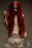 Red haired zombie woman in white cotton dress. In studio royalty free stock photo