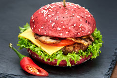 Red hamburger with chili on stone table with black background. Fastfood meal. Delicious Hamburger. Gourmet hamburger. Royalty Free Stock Images